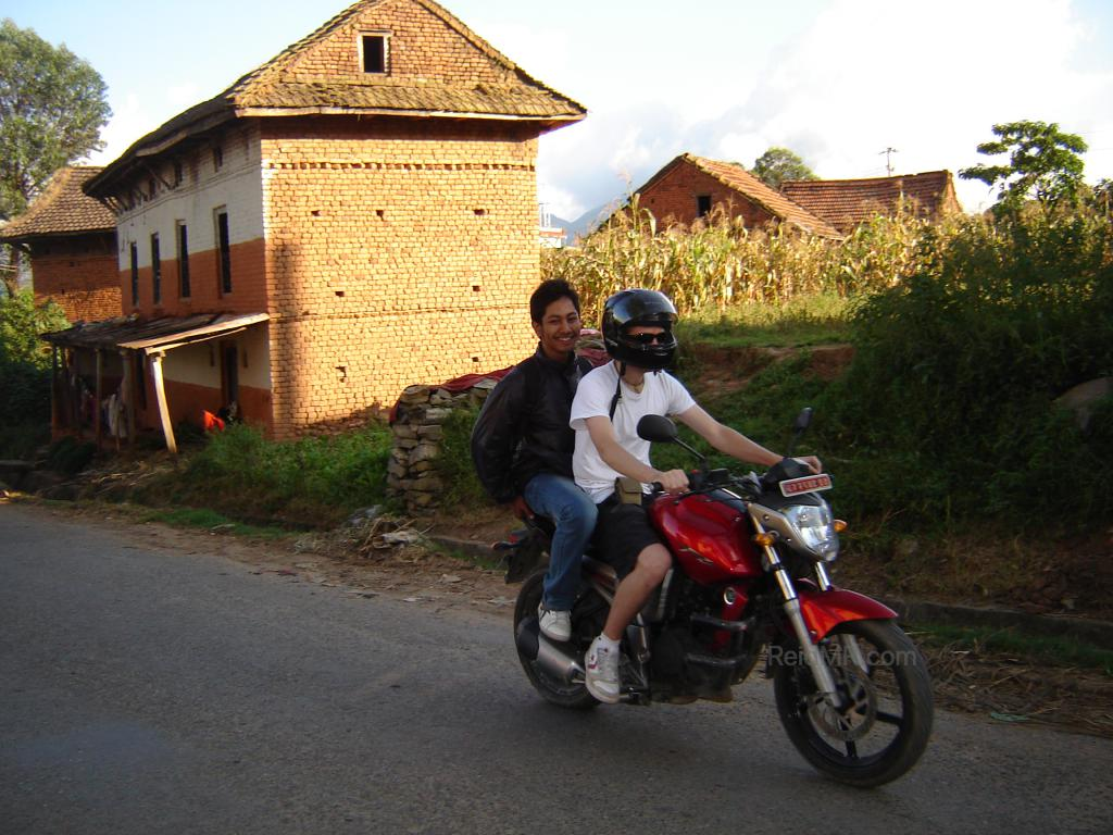 Driving Rojesh's motorcycle on the streets, with greenery and a building in the background