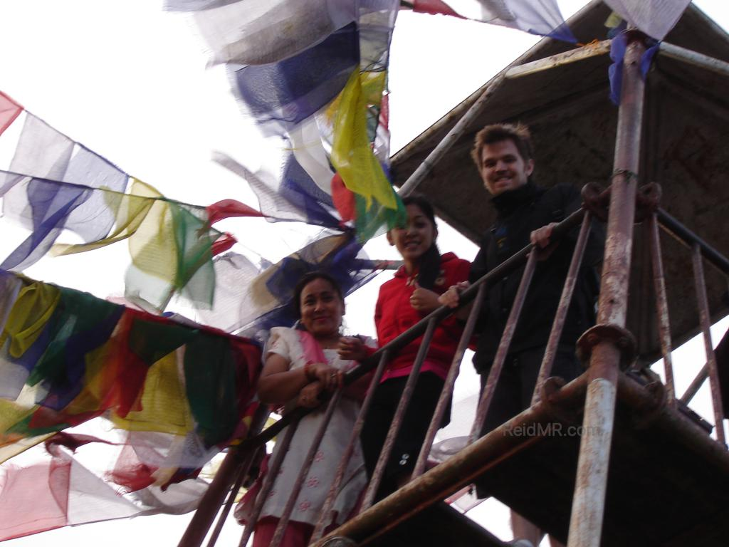 Urika, Mamu and I peering down from a tower with prayer flags waving