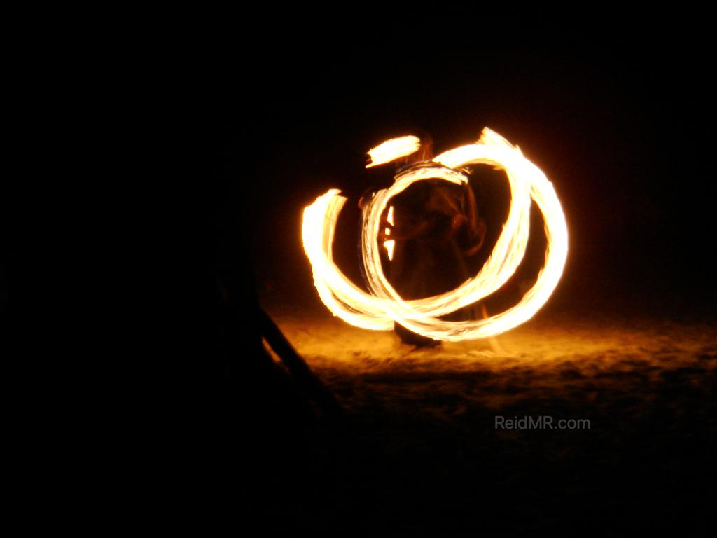 Fire dancer at night, with the light trail frozen by the camera