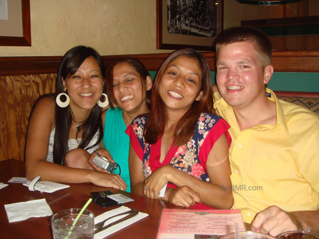 With three friends at a restaurant, sitting on a booth made for two, but all four of us together.