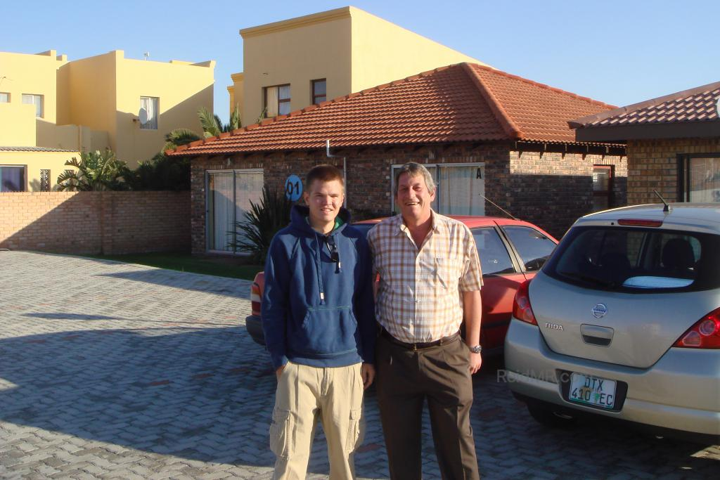 With Marius, the complex caretaker. Photo with car and some of the student village homes in the background.