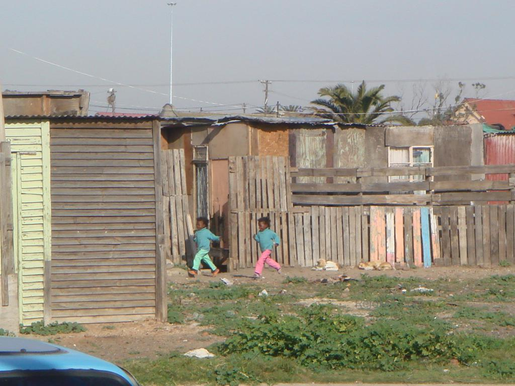 Young kids running through the township. Image of happiness in poverty.