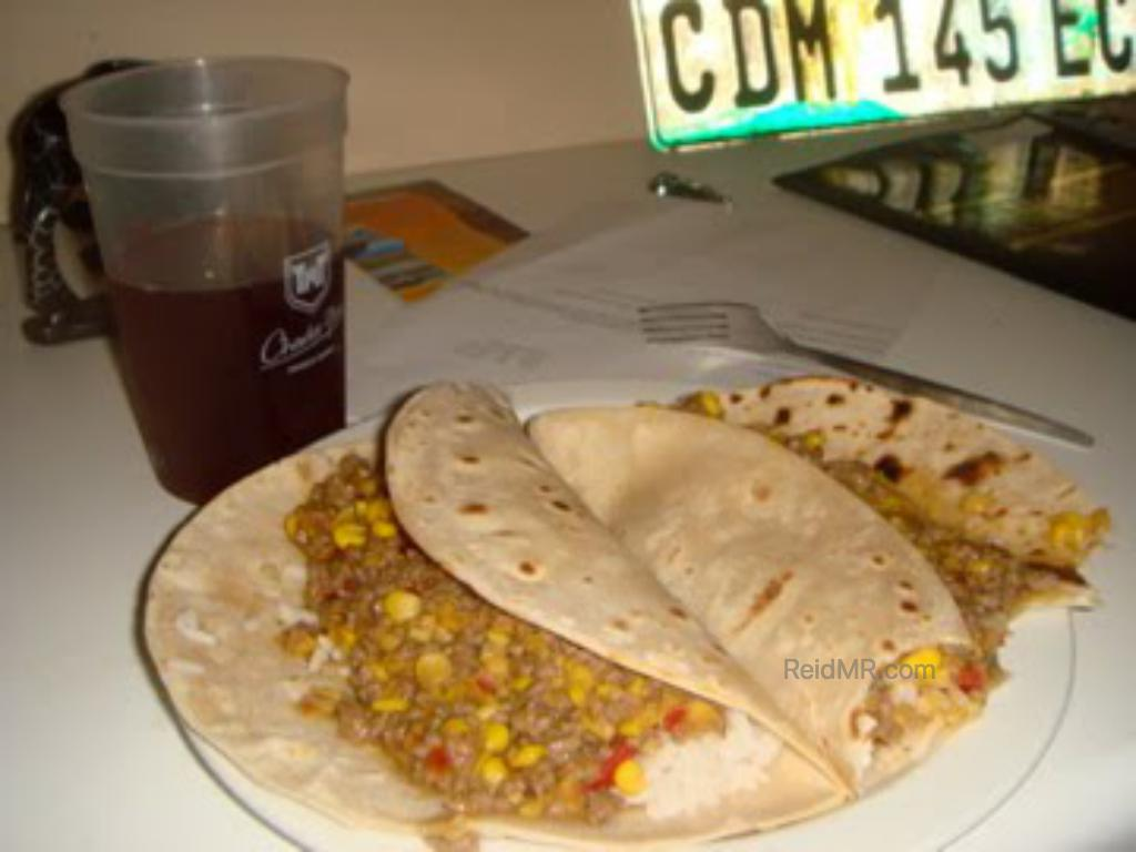 A meal, taco like, with some filling and rice.