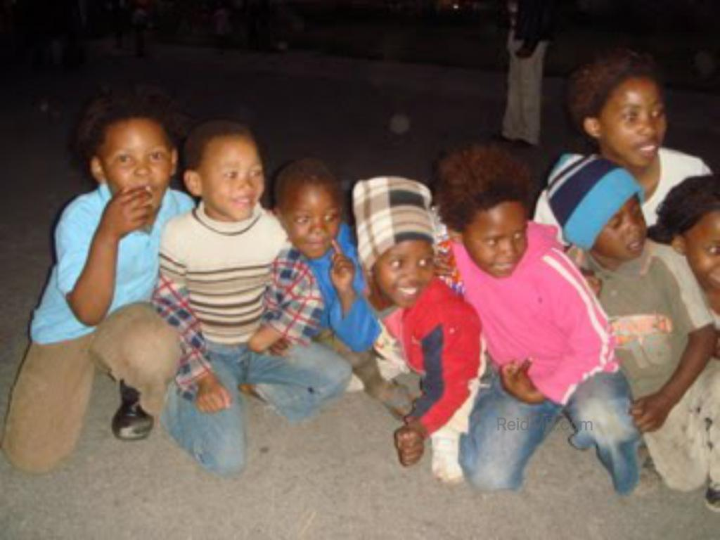 A group of local kids squatting and posing for a photo when we were on the township tour.