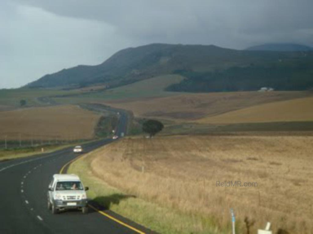 A winding road through the scenic landscape, with fields on the side and mountains in the distance.