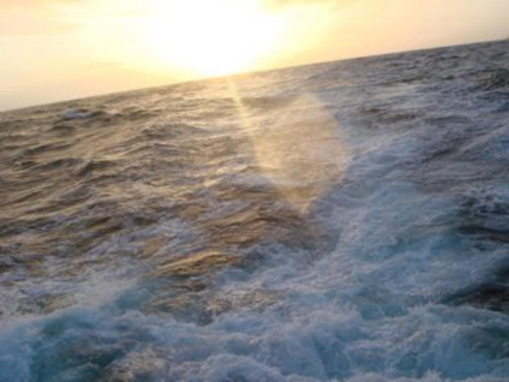 Sunset over the ocean, at a steep angle because of the stormy ocean.