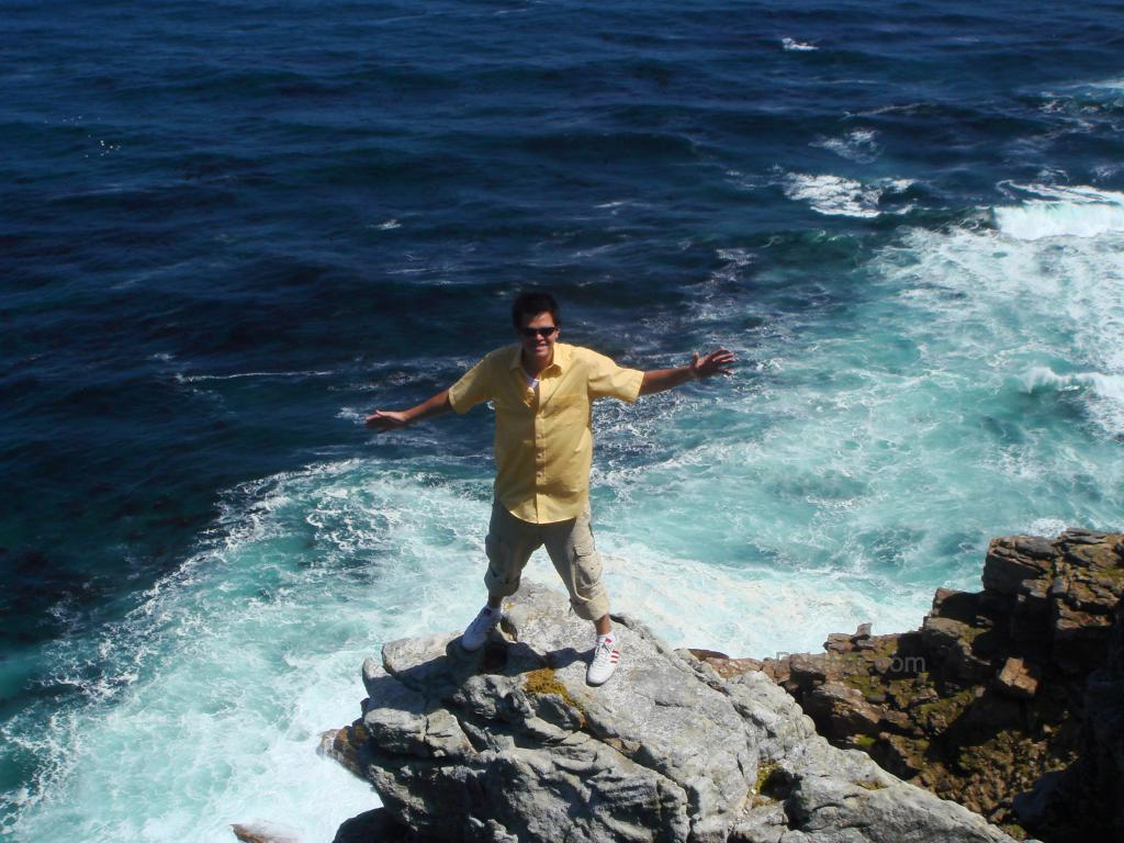 Standing on the edge of a rock jutting over the ocean.
