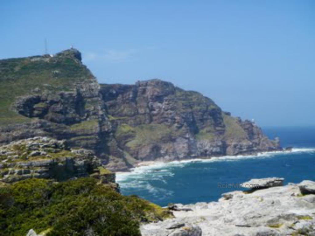 Cape Point from Cape of Good Hope, the mountainous rocky terrain jutting into the ocean.