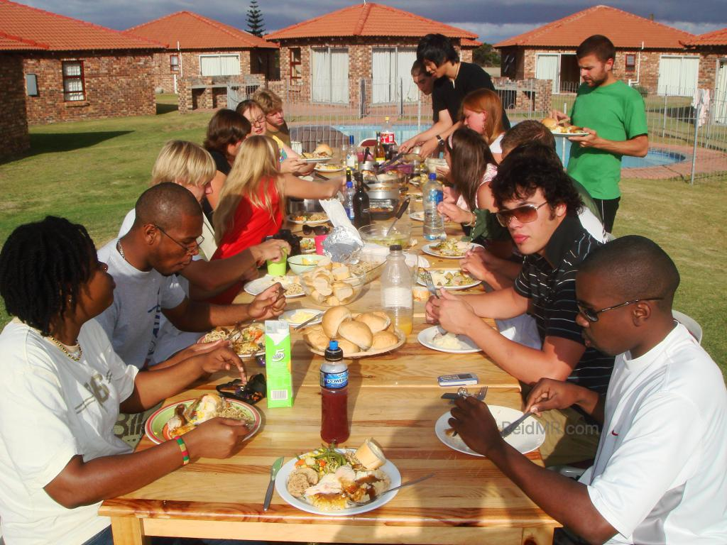 Thanksgiving Dinner, table of food, filled with people, about a dozen people