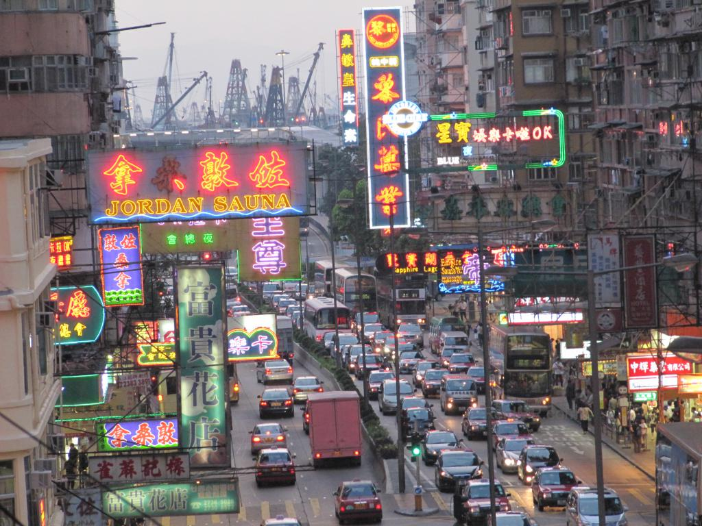 The view of a visually crowded over stimulating street in Hong Kong, with signage, wires, lights and cars.
