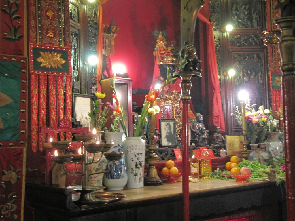 A temple in Hong Kong, the main worship area with the Buddha, fruit, incense and candles.