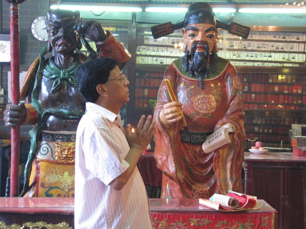 Dad praying at the temple, with a statute of a god behind him.