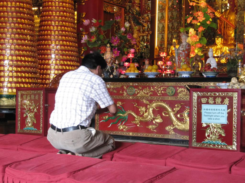 Dad praying at a temple, the altar is in front of him.