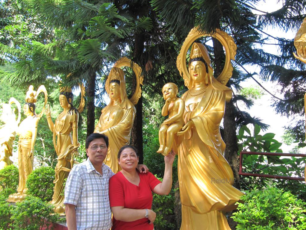 Mom and Dad with the statues in the background. She is touching the foot of a baby statue.