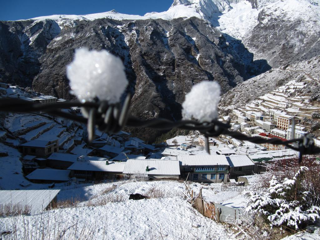 Snow on a barbed wire fence, with Namche Bazar in the background