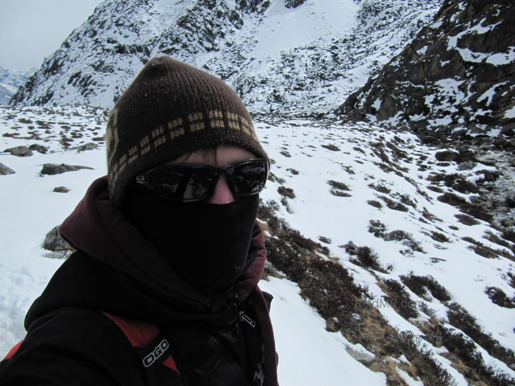 Hiking with snow on ground, me in hat, glasses and bundled up.