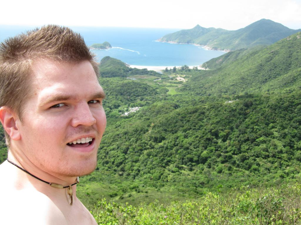 At the top of a hill, over looking the green scenery, ocean and mountains.