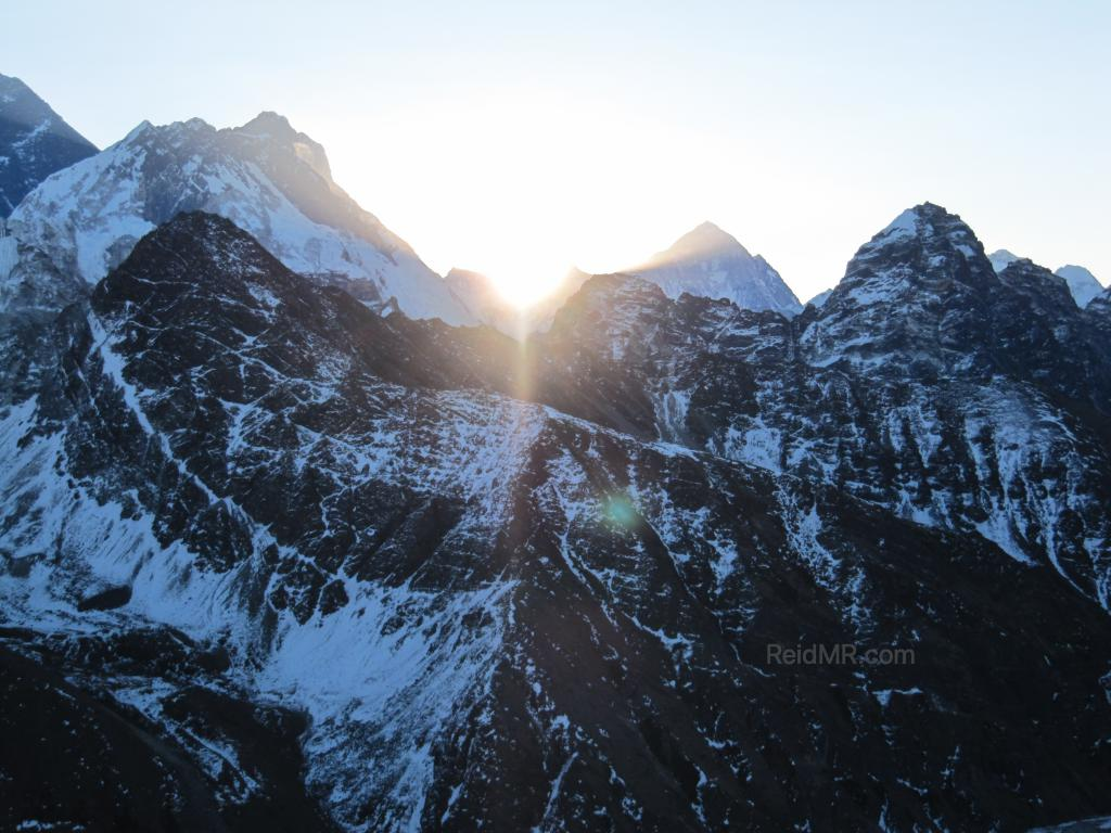 Sun coming up through the mountains, Everest is on the left