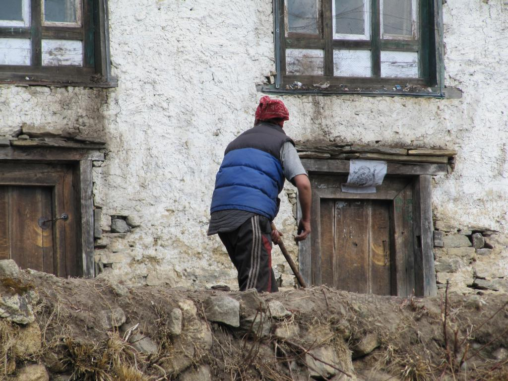 A women working up near Everest in her garden right in front of here house
