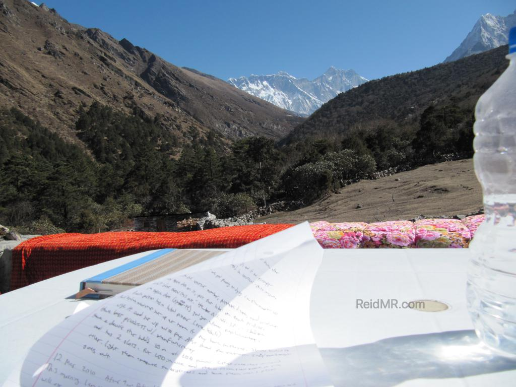 Writing in journal with Everest in background