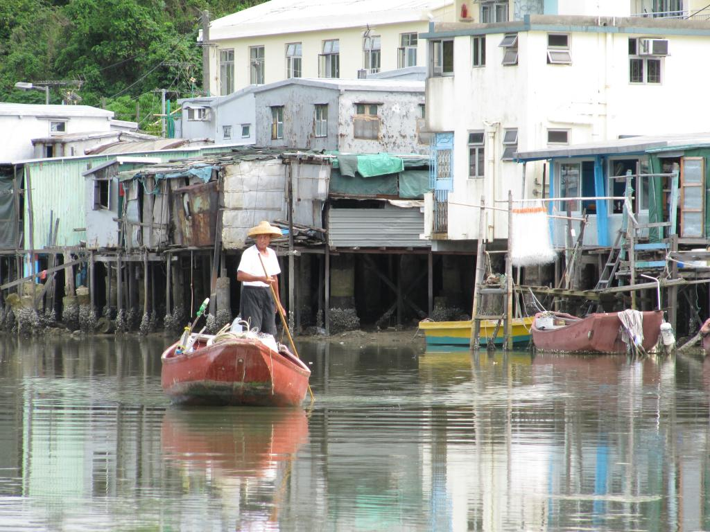 At Tai O fishing village, a man is maneuvering a boat down the river, the houses on stilts are the backdrop