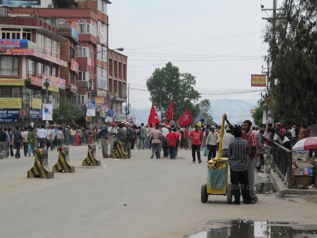 A protest, bandh, on the streets of Kathmandu. People and barricades abound.