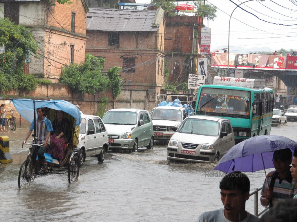 Flooded road in Kathmandu with traffic driving through