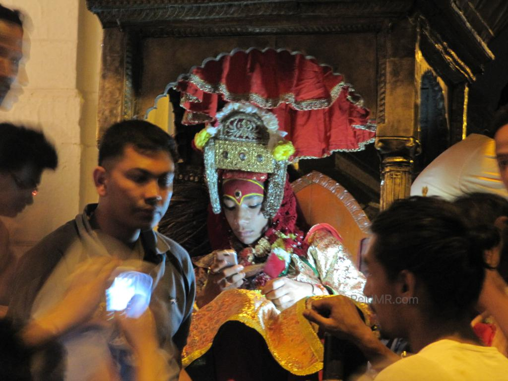 Photo of a god/goddess in Nepal. I thought it was a girl, but he is male. He is on his phone with worshippers packed around him.