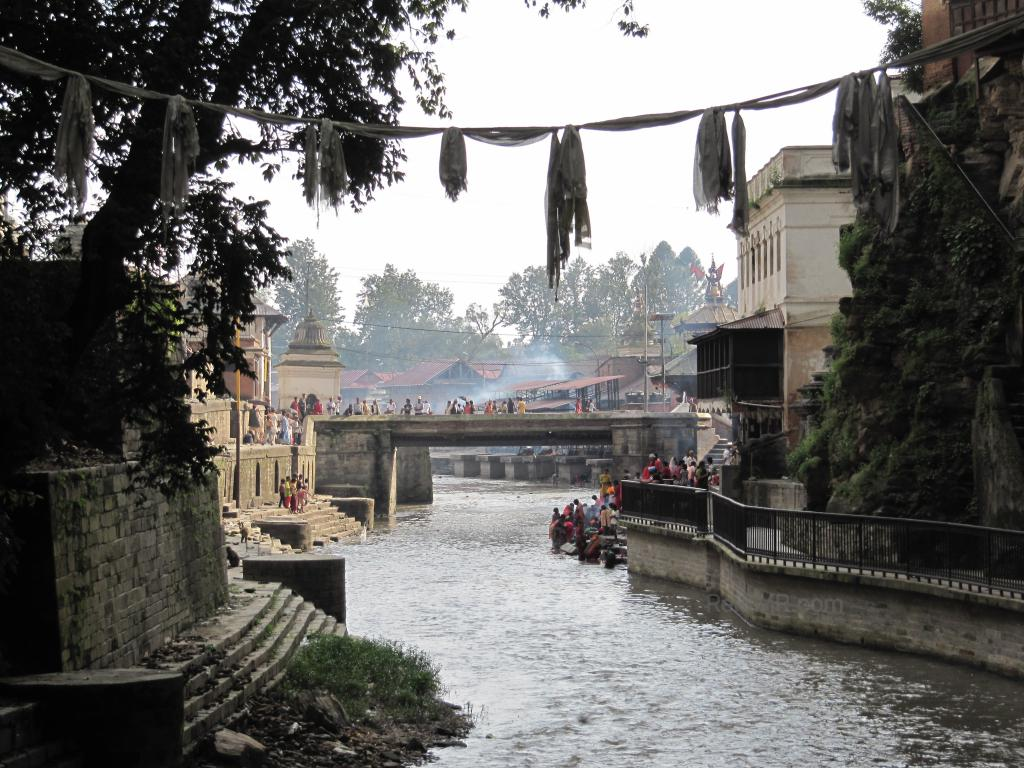 The Pashupatinath Temple, with the river running next to it. Can see people and fires burning.