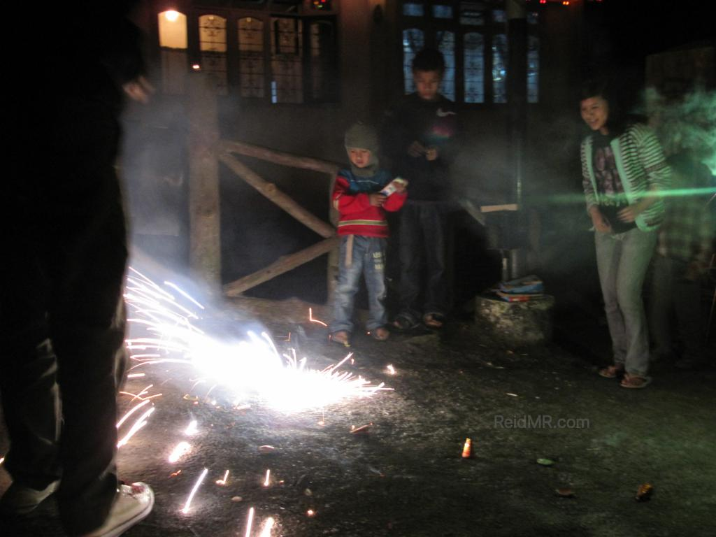 Kids lighting fireworks outside, with one burning