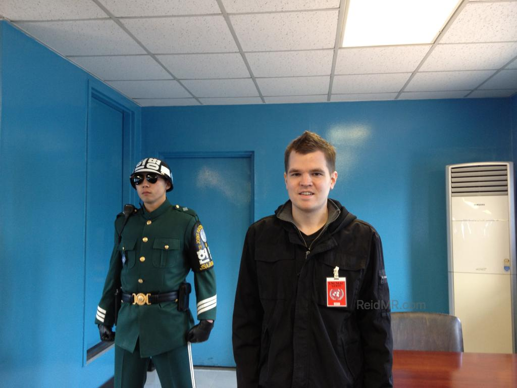 In a Blue Conference Room standing by a South Korean guard, technically in North Korea