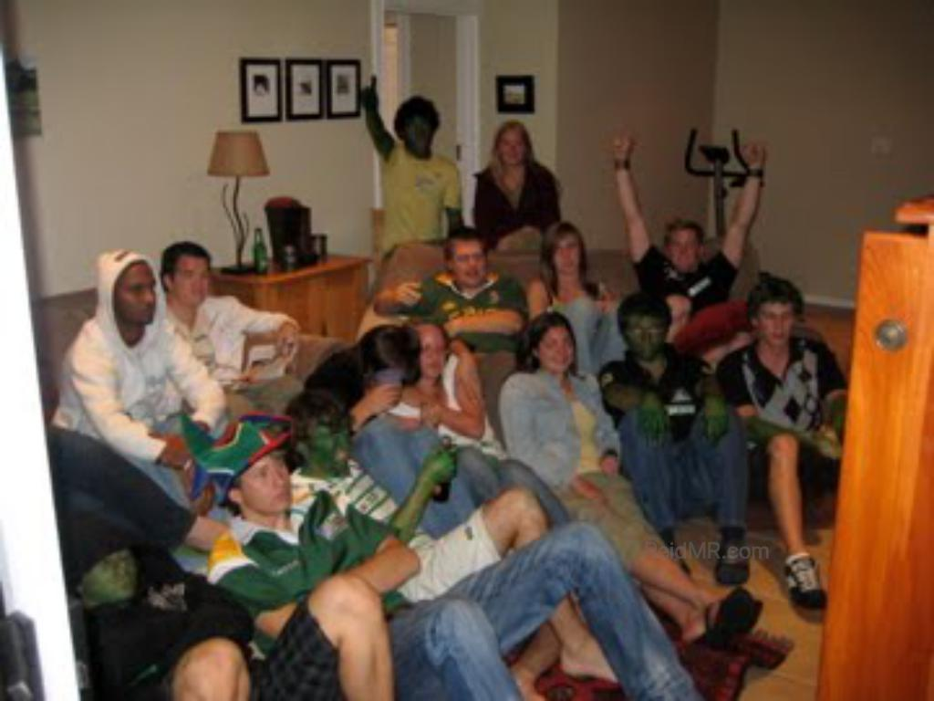 Watching the rugby game at Sean's house. Group photo of about 15 people sitting together.