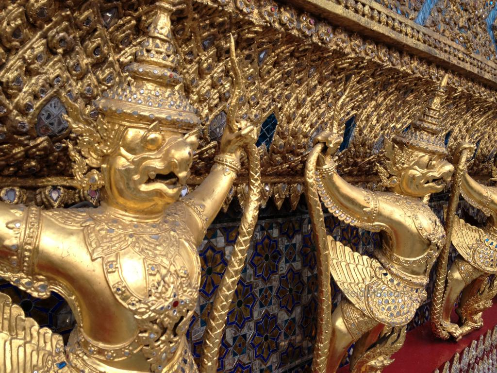 More statutes at the Temple of the Emerald Buddha, they look like they are holding up a structure and are very pained