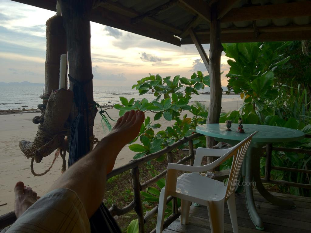 My feet with the sunset starting and the beach, hammock and deck in sight.