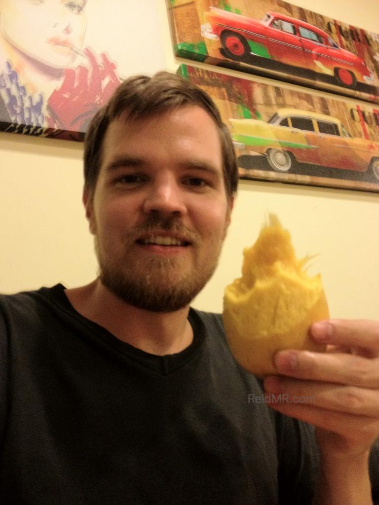 Enjoying a mango in the hostel with scruffy facial hair