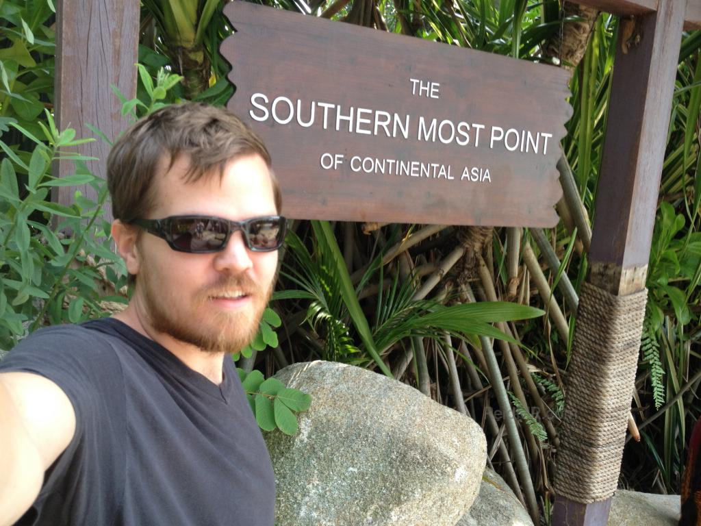 Me standing with a sign proclaiming the southernmost part of continental Asia
