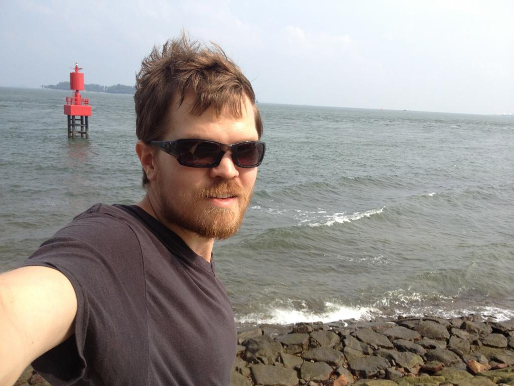 Me standing with the ocean and rocks in the background. The real southernmost point.