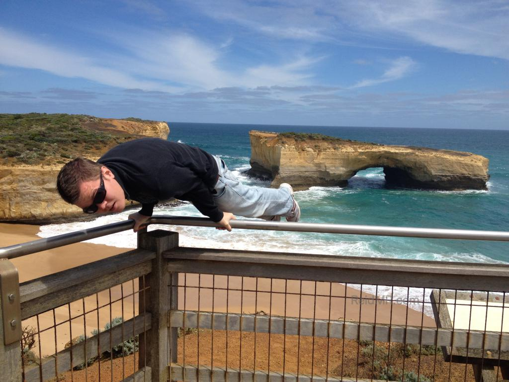 The London Bridge on the Great Ocean Road with me doing an elbow lever on a railing.