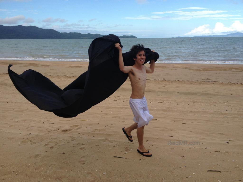 Ben playing on the beach with a sheet.